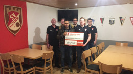 Symbolische Spendenscheckübergabe: Tyrone Winbush (5. Vorsitzender des BÜRGERDIENST e.V.) übergibt den Spendenscheck an die Repräsentanten des SV Ellscheid.