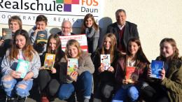 Das Foto zeigt Erwin Borsch vom Vorstand des Bürgerdienst e.V., Lehrerin Julia Pitzen, den stellvertretenden Schulleiter Thomas Follmann (rechts) und Leseratten der Realschule bei der Spendenübergabe.