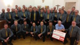 Das Foto zeigt die Mitglieder des MGV Lutzerath e. V., die Erwin Borsch (4. Vorsitzender, Bürgerdienst e. V.) in der alten Schule in Lutzerath willkommen heißen, um sich gemeinsam für die großzügige Spende zu bedanken.