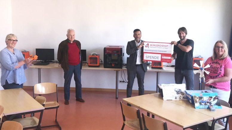 Symbolische Spendenübergabe in der Augustiner-Realschule Plus Hillesheim: Tyrone Winbush (Vorstandsmitglied des BÜRGERDIENST e.V.) übergab den Spendenscheck für das 3D-Druck-Projekt an Mario Bischoff (rechts), dem für das Projekt zuständige Lehrer. Joachim von Schnakenburg vom Rotary Club Daun-Eifel, Initiator des Projekts, kam ebenfalls zur Spendenübergabe.