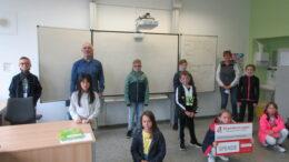 Zu sehen sind die kommissarische Schulleiterin, Ursula Ackermann, sowie Kinder der Schule und Werner Peters (Bürgerdienst Lepper e. V.) bei der symbolischen Spendenübergabe