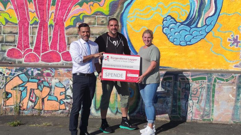 Tyrone Winbush (Bürgerdienst Lepper e. V.) bei der Übergabe des Spendenschecks an Susanne Engeln und Thomas Burch vom Haus der Jugend in Daun.
